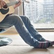 Stock Photo: Low section of mplaying guitar