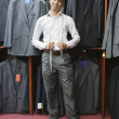 Portrait of young man posing with suits hanging in background — Foto Stock