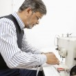 Profile of middle aged tailor using sewing machine — Stock Photo #21877535