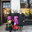 Portrait of florist standing in front of her shop - Stock Photo