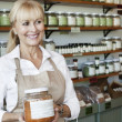 Stock Photo: Happy senior salesperson with jar looking away in spice store