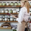 Side view of senior female employee going through list of spices in store — Stock Photo #21878371