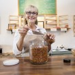 Portrait of a happy female employee pouring spice with scoop in jar - Stock Photo