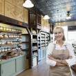 Portrait of a happy senior female spice merchant standing with arms crossed in store — Stock Photo #21878403