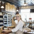 Portrait of senior spice merchant standing at counter in store — Stock Photo #21878433