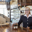 Portrait of happy female owner standing at counter with spice jar in store — Stockfoto #21878447