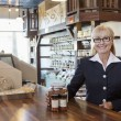 Стоковое фото: Portrait of happy female owner standing at counter with spice jar in store