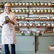 Retrato de un mercante senior de pie feliz con tarro de la especia en la tienda — Foto de Stock