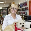 Portrait of senior woman with dog in pet shop - Stock Photo