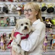 Senior pet shop owner standing with dog - Stock Photo