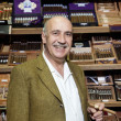 Foto de Stock  : Portrait of male owner of tobacco shop standing with cigar boxes in background