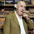 Portrait of mature tobacco shop owner smoking cigar in store - Stock Photo