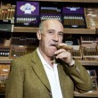 Portrait of a mature man smoking cigar in tobacco store - Stock Photo