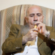 Mature man igniting cigar while sitting on armchair — Stockfoto