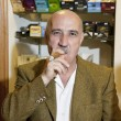 Portrait of mature tobacco store owner smoking cigar - Stock Photo