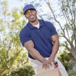 Happy young African American male pushing handtruck — Stock Photo