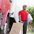 Young African American male standing with packages near delivery truck — Stock Photo #21878841