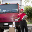 Stock Photo: Young delivery man looking at delivery list on clipboard with truck in background