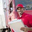 Portrait of a happy African American man holding clipboard with delivery truck in background — Stock Photo #21878863