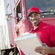 Portrait of a happy African American man holding clipboard with delivery truck in background — Stock Photo