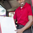 Young African American man sitting in delivery truck with box — Stock Photo #21878877