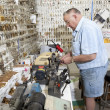 Stock Photo: Side view of senior locksmith working in store