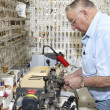 Side view of senior locksmith making key in store — Stock Photo