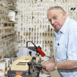 Senior locksmith looking away while making key in store — Stock Photo