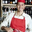 Portrait of a happy young waiter with bottle and glass — Stock Photo