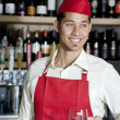 Happy handsome bartender holding glass of wine in bar — Stock Photo