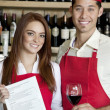 Portrait of young wait staff with wine glass and menu card in bar — Stock Photo #21879145