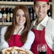 Portrait of a young wait staff with wine glass and pizza — Stock Photo #21879157