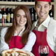 Stock Photo: Portrait of young wait staff with wine glass and pizza