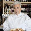 Portrait of a confident chef with pizza — Stock Photo