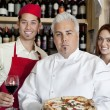 Portrait of a confident chef holding pizza with wait staff in background — Stock Photo