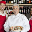 Stock Photo: Portrait of happy chef holding pizzwith wait staff