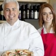 Portrait of a happy chef holding pizza with beautiful waitress — Stock Photo