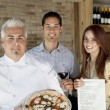 Portrait of happy chef holding pizza with young couple — Stock Photo