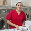 Portrait of Hispanic female employee with towel in Laundromat — Stock Photo #21879321