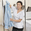 Portrait of happy young womhanging shirt in front of washing machines in Laundromat — Stock Photo #21879379