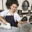 Portrait of a happy woman wearing apron ironing in front of washing machines — Stock Photo