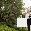 Senior real estate agent standing by sign board reading from clipboard — Stock Photo