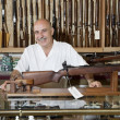 Portrait of happy mature owner of gun shop — Stock Photo