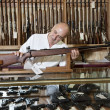 Stock Photo: Mature gun shop owner looking at rifle in store