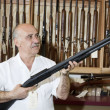 Mature gun store owner looking at weapon in shop — Stock Photo
