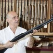 Stock Photo: Mature gun store owner looking at weapon in shop