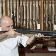Mature gun shop merchant with rifle aiming — Stock Photo