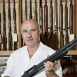 Portrait of a mature gun merchant with rifle — Stock Photo
