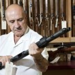 Mature gun shop merchant looking at rifle in store — Stock Photo