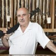 Portrait of a mature man with rifle on shoulder in gun store - Stock Photo